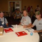 John Hughes, Bob Vaxter and Glen Hutchins enjoy photos from Charlie Co, 3rd Tanks